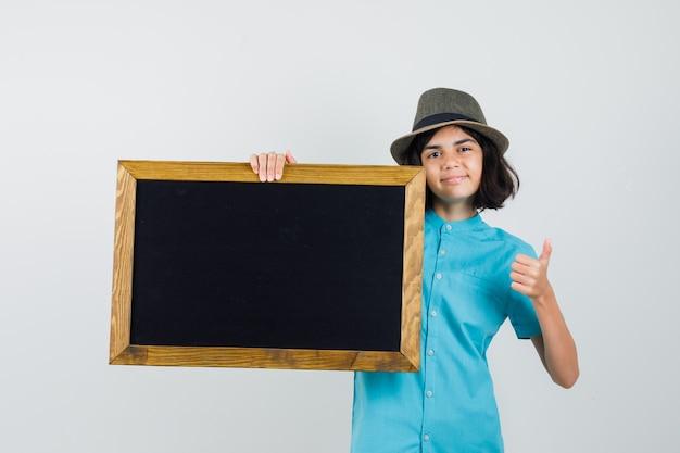 Giovane signora che tiene cornice vuota mentre mostra il pollice in su in camicia blu, cappello e sembra ottimista.