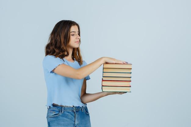Giovane signora che tiene i libri in maglietta, jeans e guardando attento. vista frontale.