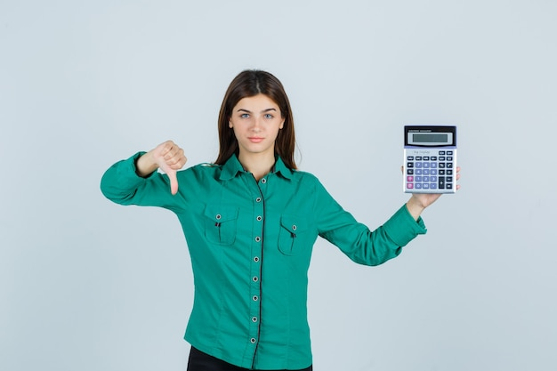 Young lady holding calculator, showing thumb down in green shirt and looking displeased. front view.