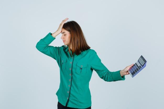 Молодая леди держит калькулятор, держа руку на лбу в зеленой рубашке и выглядя разочарованной. передний план.