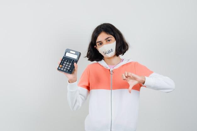 パーカー、フェイスマスクで親指を下に表示し、不機嫌そうに見える間、電卓を保持している若い女性。
