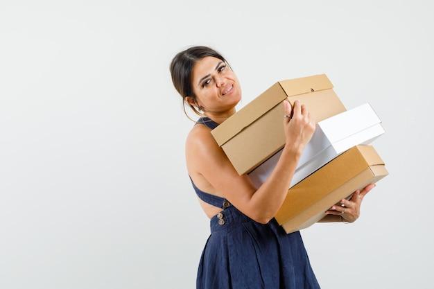 Giovane donna che tiene scatole di cartone in abito e sembra allegra