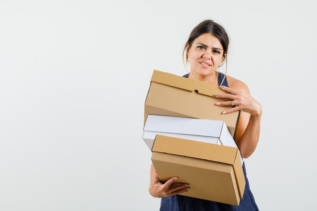 Giovane donna che tiene scatole di cartone in abito