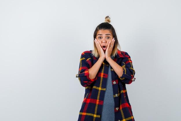 Giovane donna che tiene le guance con i palmi in camicia casual a quadri e sembra scioccata, vista frontale.