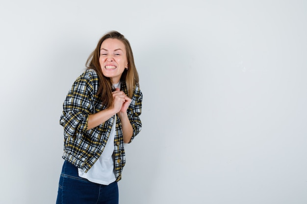 Giovane donna che tiene le mani giunte sul petto in t-shirt, giacca, jeans e che sembra felice, vista frontale.
