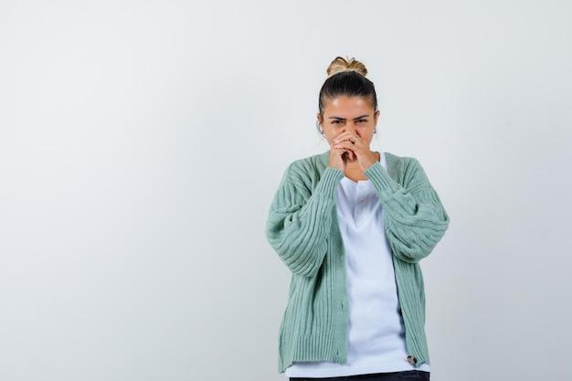 Молодая дама, держащая сцепленные руки возле рта в футболке, куртке и уверенная в себе
