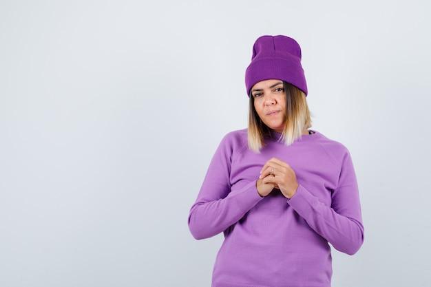 紫色のセーター、ビーニーで胸に握りしめられた手を握り、焦点を合わせて見ている若い女性、正面図。
