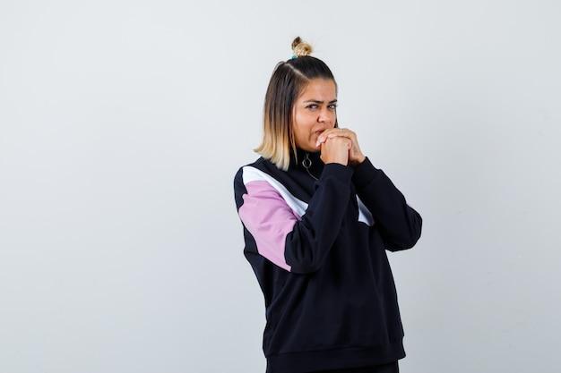 パーカーのセーターのあごに握りしめられた手を握り、集中しているように見える若い女性。