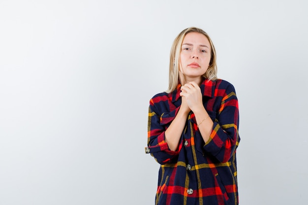 Giovane donna che tiene le mani giunte per pregare in camicia a quadri e guardando pacifica, vista frontale.