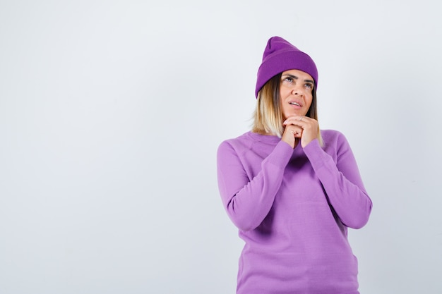 Giovane donna che tiene le mani giunte in gesto di preghiera in maglione viola, berretto e guardando speranzoso, vista frontale.