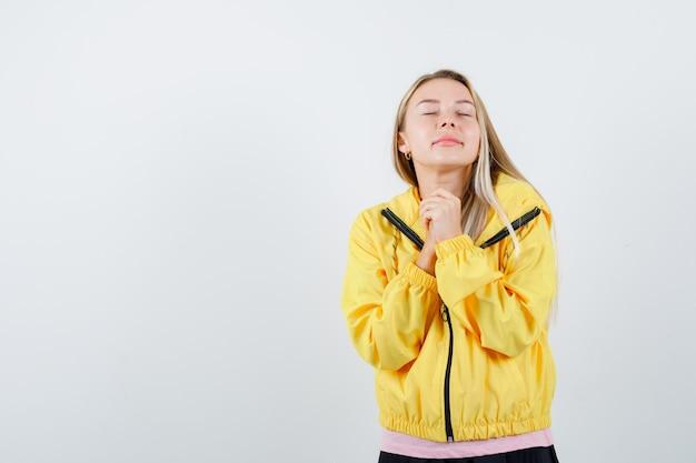 Giovane donna che tiene le mani giunte vicino al petto in t-shirt, giacca e sembra speranzoso