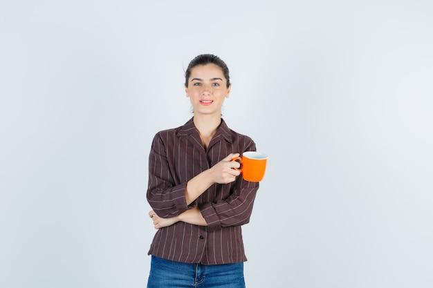 젊은 여성이 컵을 들고 셔츠, 청바지를 입은 카메라를 바라보며 애타게 바라보고 있습니다.