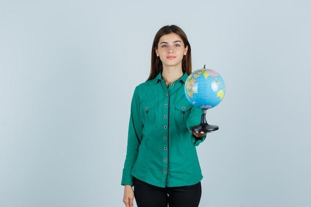 Молодая дама держит земной шар в рубашке и выглядит уверенно. передний план.