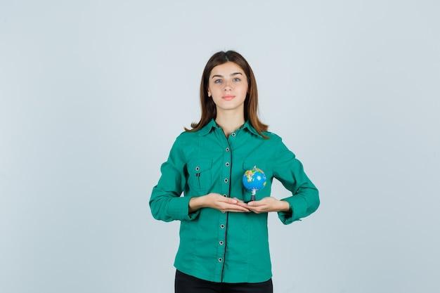 シャツに地球儀を持って、喜んでいる若い女性。正面図。