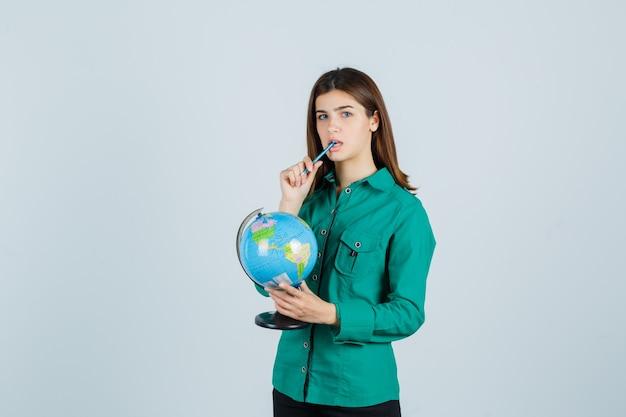 젊은 아가씨 지구 글로브를 들고 셔츠에 입에 펜을 유지 하 고 사려 깊은, 전면보기를 찾고.