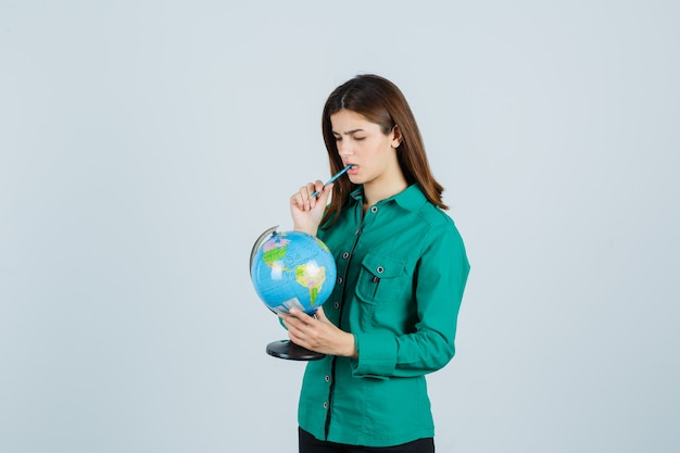 Young lady holding earth globe, keeping pen in mouth in shirt and looking pensive. front view.