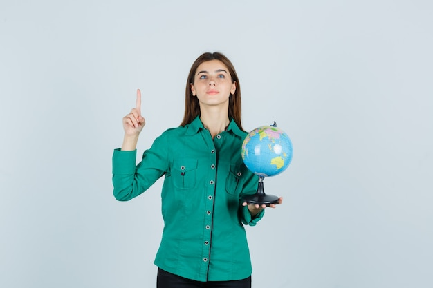 Young lady holding earth globe, pointing up in shirt and looking pleased. front view.