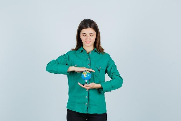 Giovane donna che tiene il globo terrestre in camicia e che sembra fiducioso. vista frontale.
