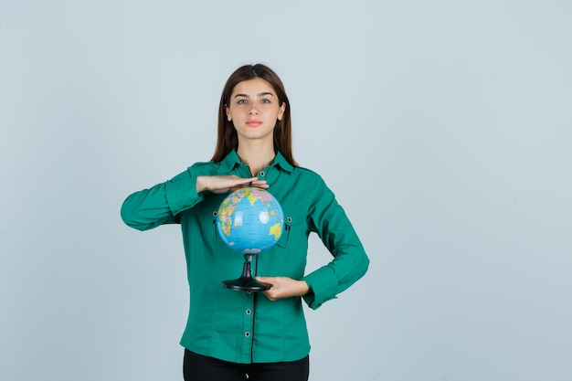 Young lady holding earth globe in shirt and looking confident. front view.
