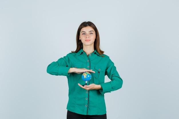 Giovane signora che tiene il globo terrestre in camicia e che sembra soddisfatto. vista frontale.