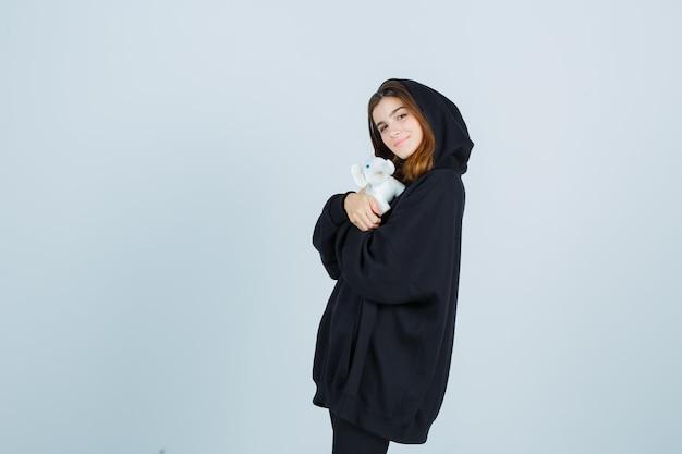 Молодая леди держит игрушку слона на груди в негабаритной толстовке с капюшоном, штанах и выглядит красиво, вид спереди.