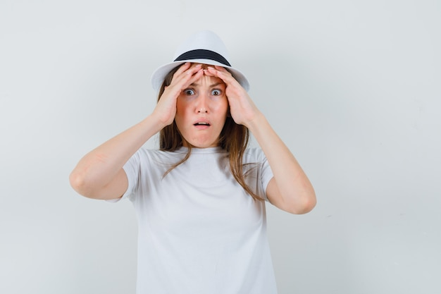 흰색 티셔츠 모자에 손으로 얼굴을 잡고 곰곰이 찾고 젊은 아가씨
