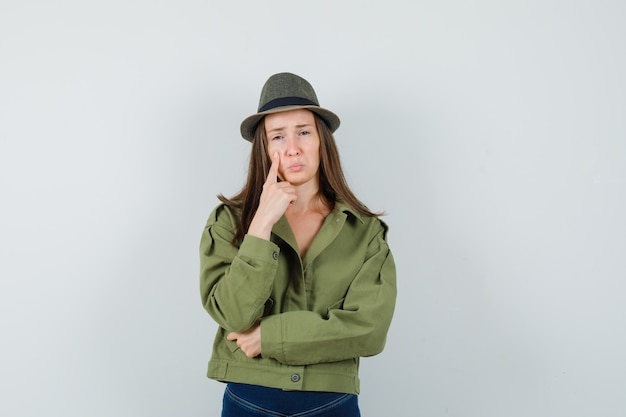 Young lady holding finger on cheek in jacket pants hat and looking upset