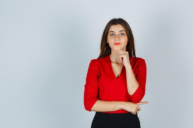 Giovane donna che tiene il dito sotto il mento in camicetta rossa, gonna e sembra carina