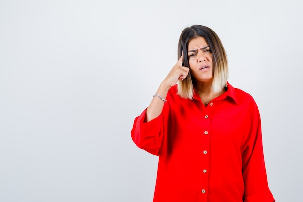 Young lady holding finger on head in red oversize shirt and looking thoughtful , front view.
