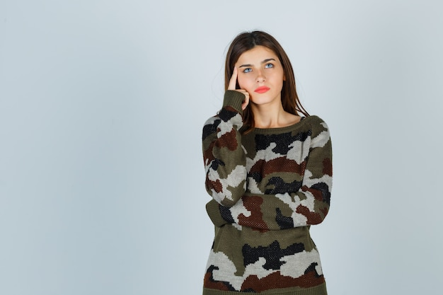 Giovane donna che tiene il dito sulle tempie in maglione, gonna e guardando pensieroso