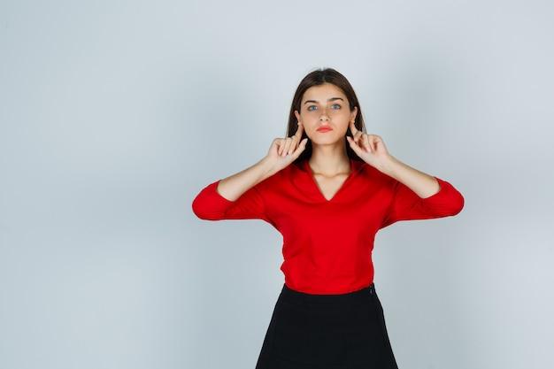 Молодая дама держит пальцы за ушами в красной блузке, юбке и выглядит смешно