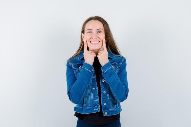 Giovane donna che tiene le dita sulle guance in camicetta, giacca e sembra allegra, vista frontale.