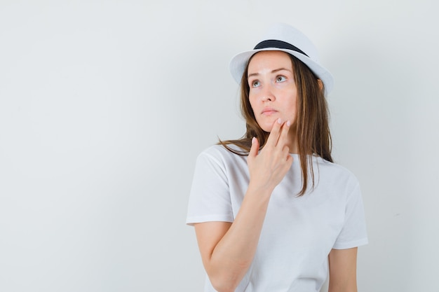 Young lady holding fingers on chin in white t-shirt hat and looking pensive