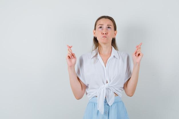 Giovane donna che tiene le dita incrociate in camicetta e gonna e sembra speranzosa