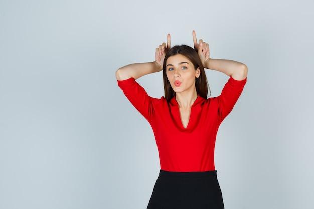 Giovane donna che tiene le dita sopra la testa come corna di toro in camicetta rossa, gonna e sembra divertente