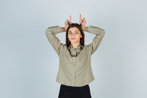 Young lady holding fingers over head as bull horns in shirt, skirt and looking amused