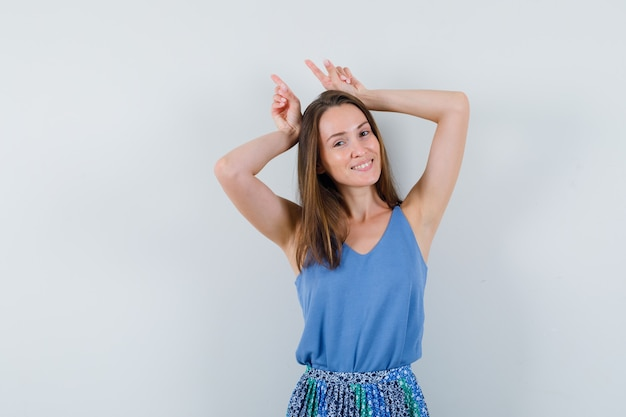 Young lady holding fingers over head as bull horns in singlet, skirt and looking funny
