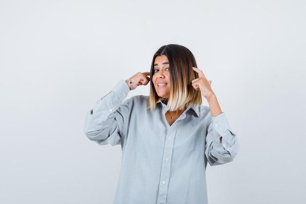 Giovane donna che tiene le dita sulla testa in camicia oversize e sembra allegra. vista frontale.