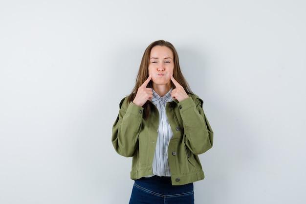 シャツ、ジャケットの吹き飛ばされた頬に指を持って、素敵に見える若い女性。正面図。