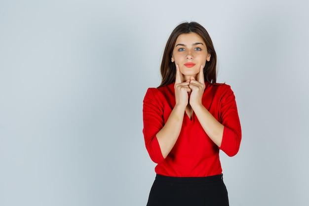 Молодая дама держит пальцы на щеках в красной блузке, юбке и выглядит красиво