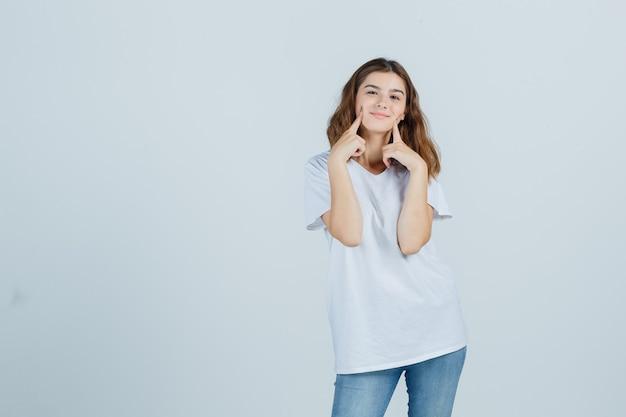 Молодая дама держит пальцы на щеках в футболке, джинсах и выглядит мило. передний план.
