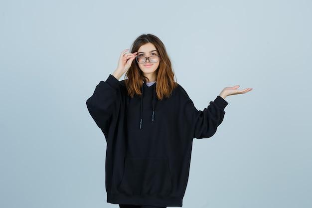 Молодая леди, держащая пальцы на очках, делая вид, что показывает что-то в огромной толстовке с капюшоном, штанах и выглядит радостной, вид спереди.