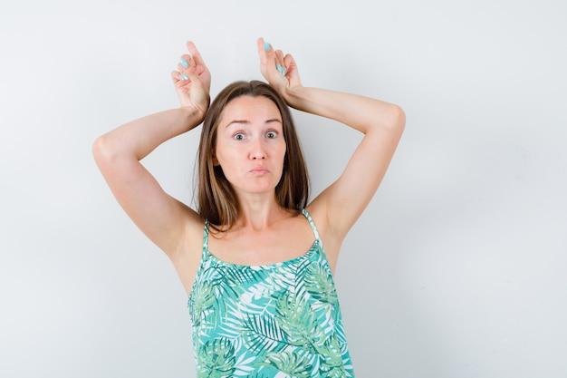 ブラウスの角のように頭の上に指を持って、おかしな顔をしている若い女性。正面図。