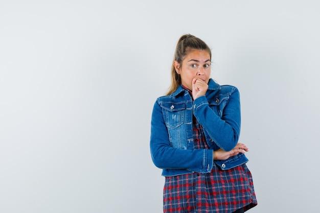 Giovane donna che tiene il pugno sul mento in camicia, giacca e sguardo esitante, vista frontale.