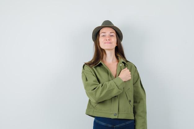 ジャケットパンツの帽子で胸に拳を保持し、自信を持って見える若い女性