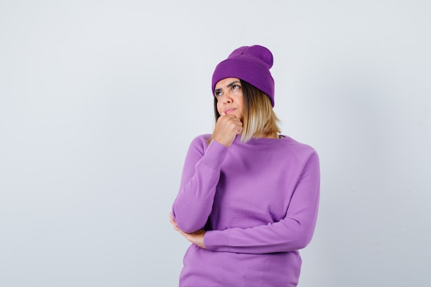 紫のセーター、ビーニーであごに拳を握り、物思いにふける若い女性。正面図。