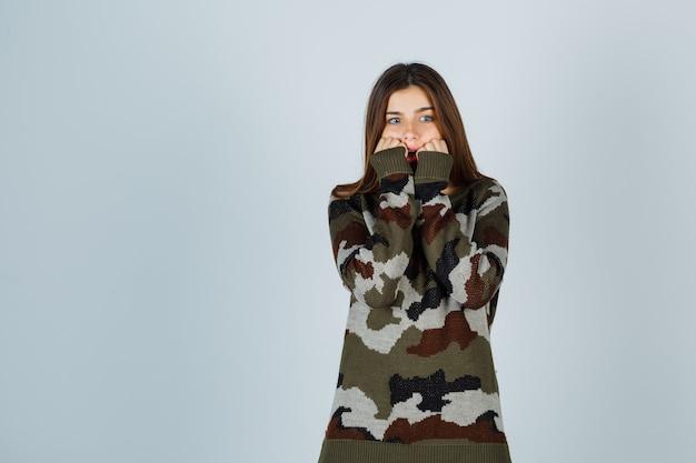 Giovane donna che tiene i pugni sulle guance in maglione e sembra spaventata