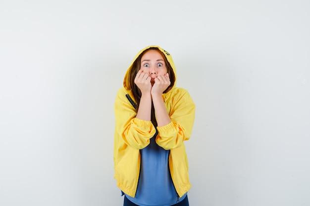 Tシャツ、ジャケット、怖い顔で頬に拳を持っている若い女性