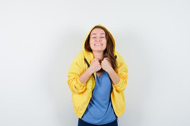 Tシャツ、ジャケット、陽気に見える胸に拳を保持している若い女性