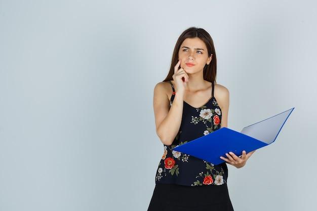Девушка держит папку, подпирает рукой подбородок в блузке и смотрит задумчиво. передний план.